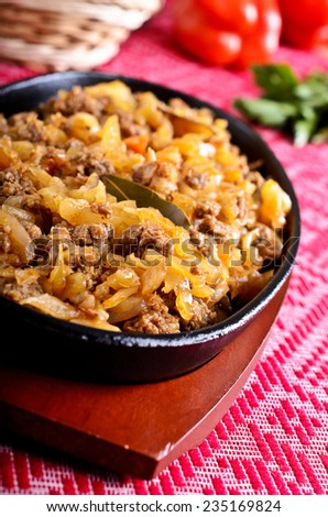 Cabbage stewed with meat in portions pan black