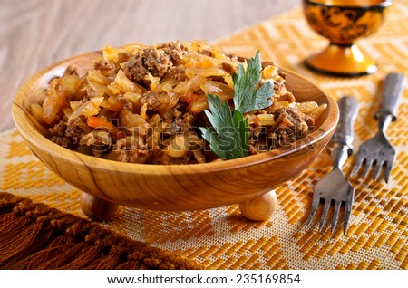 Cabbage stewed with meat in portions wooden plate - stock photo
