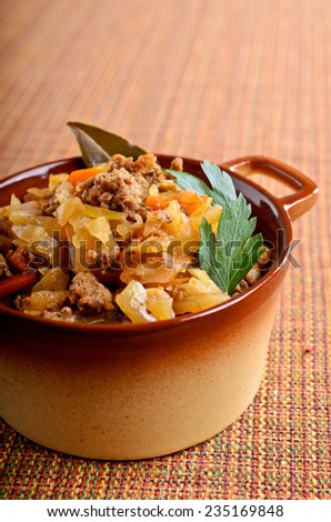 Cabbage stewed with meat in the pan portions - stock photo