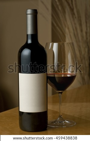 Cabernet wine bottle and glass, blank label - stock photo