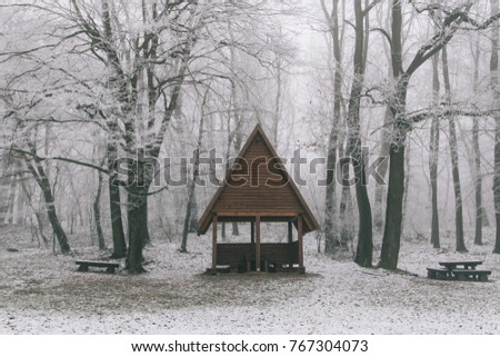 Cabin in the woods. Winter landscape with small wooden house. Rest area in forest.