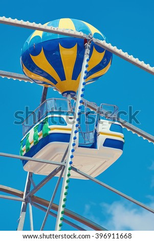 Cabin of Ferris Wheel over the Blue Sky