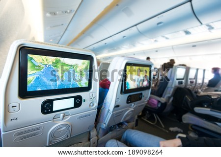 Cabin with people aboard looking at LCD monitors. Colorful flight map and film on screens. Passenger plane interior. Fast and comfortable traveling. Monitor as means of getting fun and information.