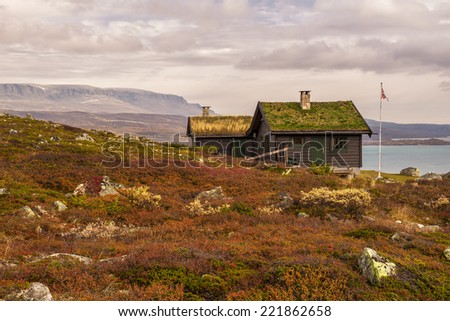 Cabin with turf roof near Hardangervidda National Park with Sloddfjorden lake in the background, Buskerud county, Norway - stock photo