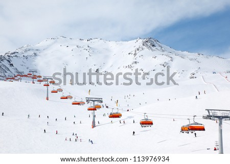 Cable car in mountains. Many skiers ride in Alps at sunny winter day. - stock photo