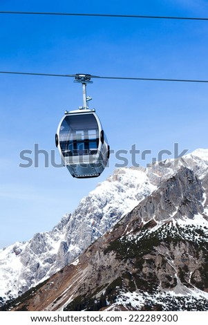Cable car on the ski resort in Austria. On the background blue sky. - stock photo