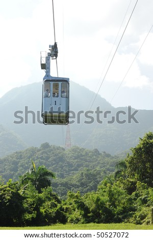 Cable car passing over jungle forest in Dominican Republic - stock photo