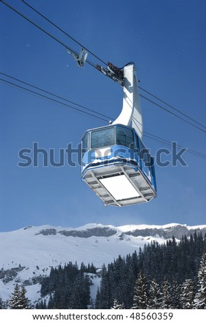 Cable car with specs of snow in Switzerland Alps - stock photo