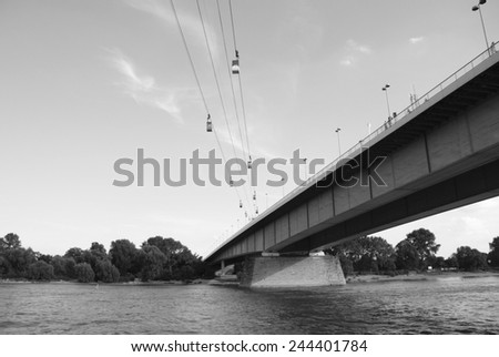 Cable cars cross the Rhine by the Zoobruecke (Zoo Bridge) in Cologne, Germany - monochrome processing - stock photo