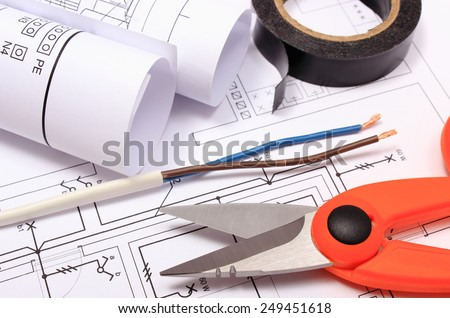 Cable cutter, electric wire and black insulating tape, rolls of electrical diagrams lying on construction drawing of house, accessories for engineer jobs - stock photo