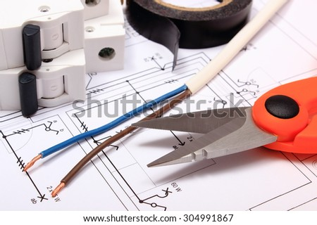 Cable cutter, electric wire and fuse, insulating tape lying on construction drawing of house, accessories for engineer jobs,