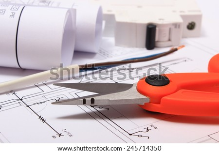 Cable cutter, electric wire and fuse, rolls of electrical diagrams lying on construction drawing of house, accessories for engineer jobs - stock photo