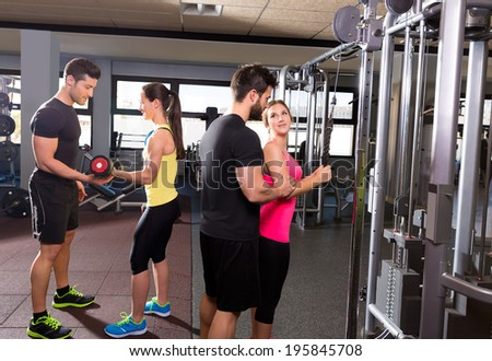 cable pulley system gym and dumbbell fitness people group with personal trainer - stock photo
