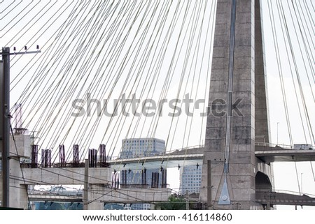 Cable stayed bridge during daylight with construction site on its side