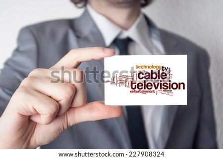 Cable television. Businessman in suit with a black tie showing or holding business card - stock photo
