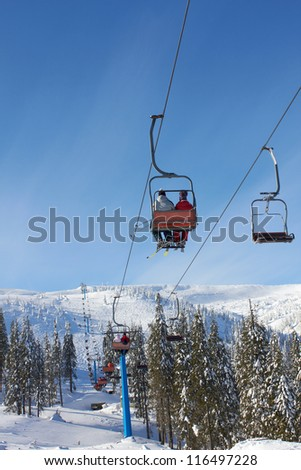 Cable-way in the mountains with skiers