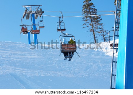 Cable-way in the mountains with skiers - stock photo