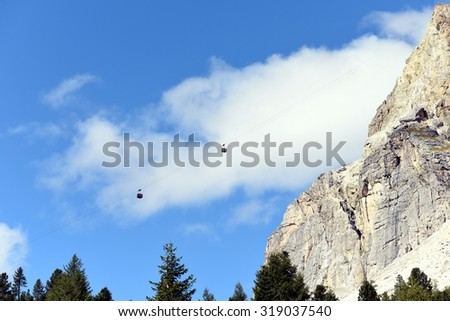 Cable way with two cable car on a cloudy and blue sky background in summer time. Ski lifts at work in a beautiful autumn day in the mountains of Cortina D'ampezzo, Italy.