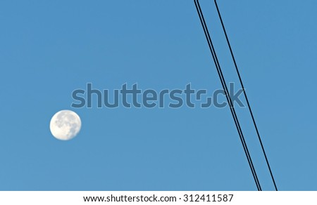 Cables of an overhead power line along the moon in a blue sky