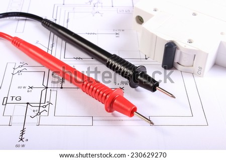Cables of multimeter and electric fuse lying on construction drawings of house, electrical drawings and tools for engineer jobs - stock photo