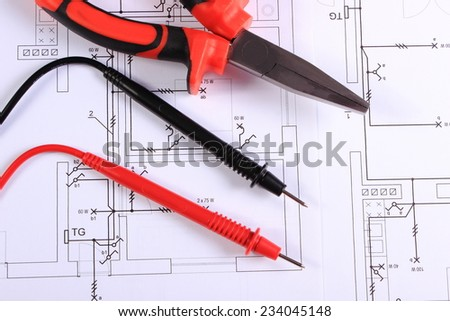 Cables of multimeter and metal pliers lying on construction drawings of house, electrical drawings and work tools for engineer jobs