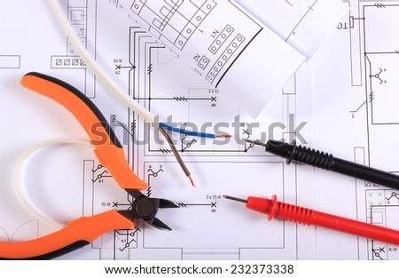 Cables of multimeter, metal pliers, electric wire and construction drawings, electrical drawings and tools for engineer jobs - stock photo