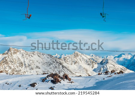 Cableway in snowy blue mountains with clouds. Winter ski resort