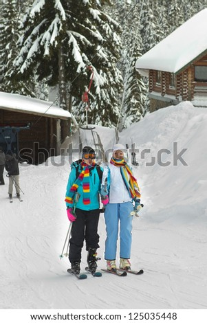 Cableway in the mountains with skiers - stock photo