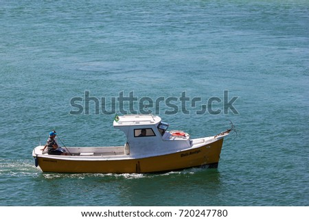 Cabo Frio, Brazil, August 15, 2016: Boat white and yellow wooden sailing in the Atlantic Ocean waters in the city of Cabo Frio, in the state of Rio de Janeiro, Brazil.