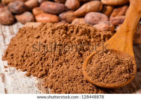 cacao beans and cacao powder in spoon over wooden background - stock photo