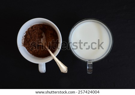 Cacao powder and milk in two cups - stock photo
