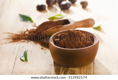 Cacao powder in  wooden bowl. Selective focus - stock photo