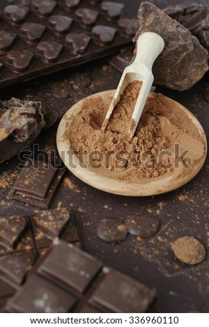 Cacao powder in wooden bowl with chopped and chips of  dark chocolate
