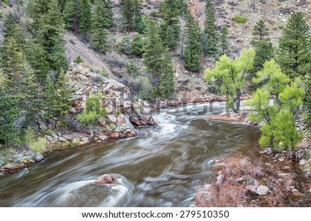 Cache la Poudre River at Big Narrows west of  Fort Collins in northern Colorado - springimie scenery with a snow melt run off - stock photo