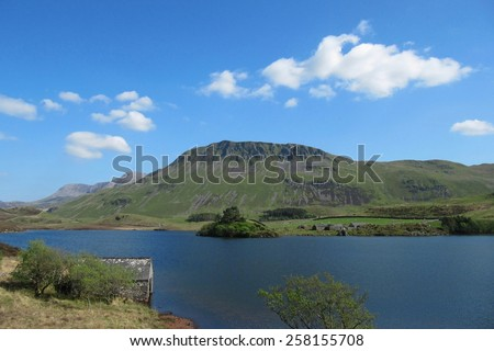 cadair idris behind a mountain lake bathed in sunshine in snowdonia national park - stock photo