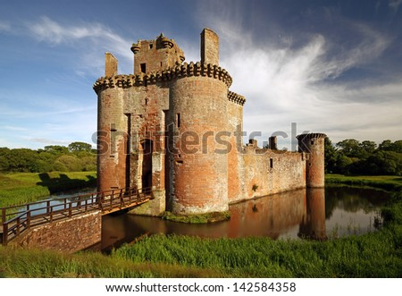 Caerlaverock Castle reflecting on the moat that surrounds the castle. Dumfrieshire, Scotland. - stock photo