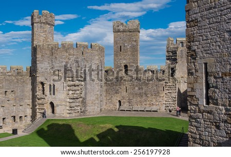 CAERNARFON, WALES - 29 SEPT. 2013: Visitors at 13th Century Caernarfon Castle, known for its polygonal towers. It is a major landmark in Wales and attracts thousands of visitors each year - stock photo