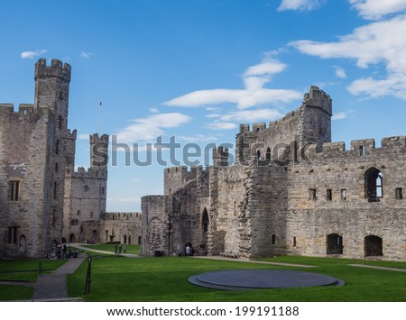 CAERNARFON, WALES - 29 SEPTEMBER 2013: Inner courtyard at Caernarfon Castle, well-known for its polygonal towers. In 1969 Prince Charles was invested here as Prince of Wales by HM Queen Elizabeth II. - stock photo