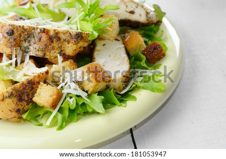 Caesar chicken salad with grated parmesan on white table