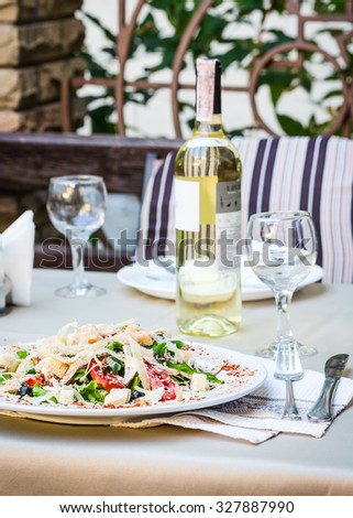 Caesar chicken salad with grated parmesan served with white wine,at the terrace restaurant