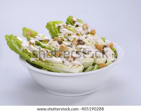 Caesar salad in a bowl with white background