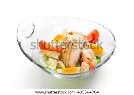 Caesar salad in a glass salad bowl on a white background