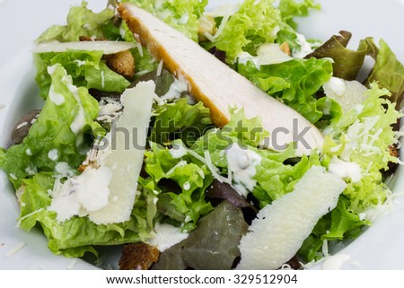 Caesar salad on a white plate. - stock photo