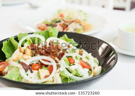 caesar salad on black bowl on dinning table with soup and beverage - stock photo
