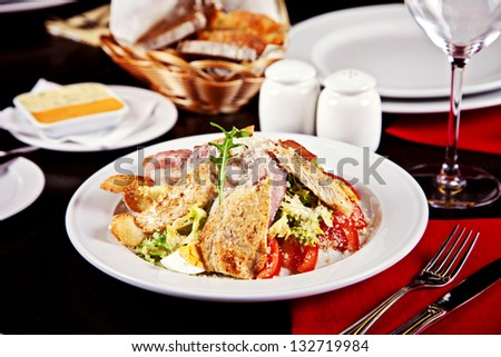 Caesar salad served on plate in restaurant - stock photo