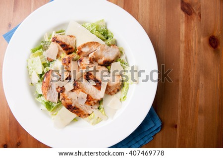 caesar salad topped with grilled chicken and shaved parmesan cheese - stock photo