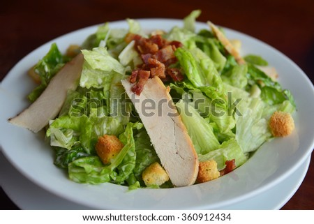 Caesar salad with chicken and bread croutons in the white bowl - stock photo