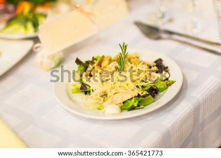 Caesar salad with chicken and greens on a table