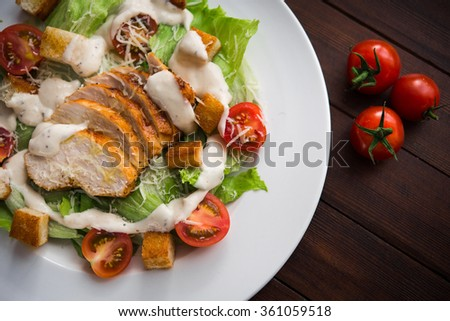 Caesar salad with chicken and tomato on wooden table