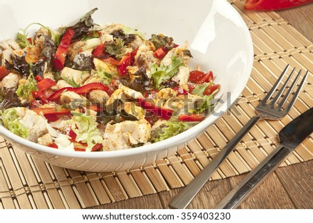 Caesar salad with chicken in white bowl on dark rustic table